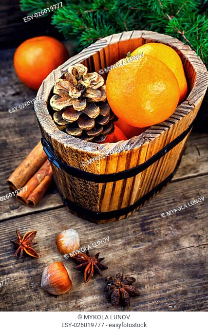 Wooden bucket with tangerines and pine cones on the background of Christmas trees and spices