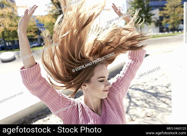Portrait of young woman with flying hair. Munich, Germany
