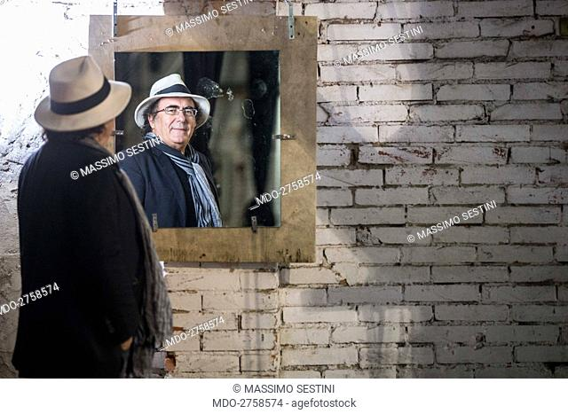 Italian singer-songwriter and actor Al Bano (Albano Carrisi) smiling looking at the image of himself reflected in a mirror