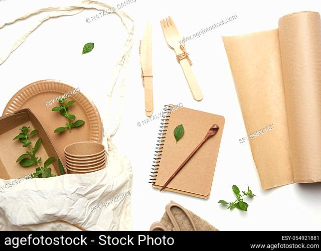 textile bag and disposable tableware from brown craft paper, green mint leaves on a whitebackground. View from above, plastic rejection concept, zero waste