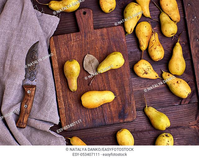 ripe yellow pears scattered on a brown wooden table, top view