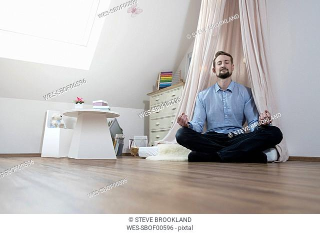 Father meditating in nursery