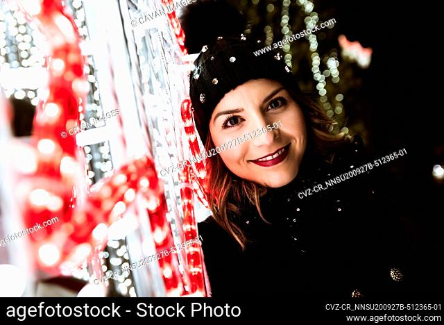 A young girl is smiling and looking at the camera with Christmas light