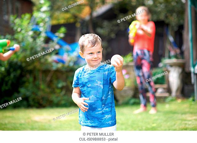 Mischievous boy holding water balloon in garden