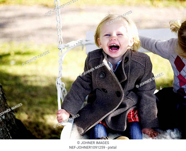 Two girls sitting on swing and playing