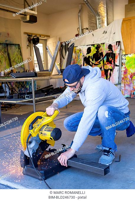 Caucasian man cutting metal with saw