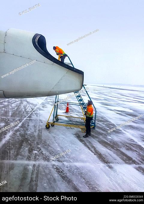 Two persons service a small aircraft parked on the tarmac in extreme winter conditions, Ontario, Canada