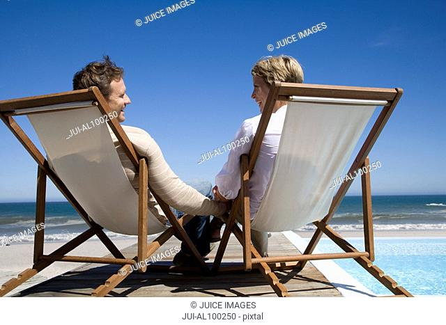 Couple in deck chairs near swimming pool