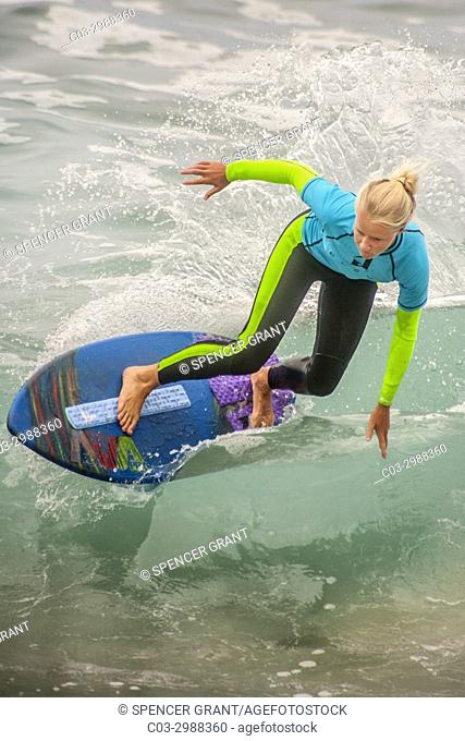Carefully keeping her balance, a blonde teen girl surfer in a wetsuit rides the waves on a skimboard in Laguna Beach, CA