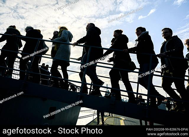 """08 February 2020, Lower Saxony, Wilhelmshaven: Family members and acquaintances of the crew of the frigate """"""""Hamburg"""""""" enter the ship via the gangway after its..."""