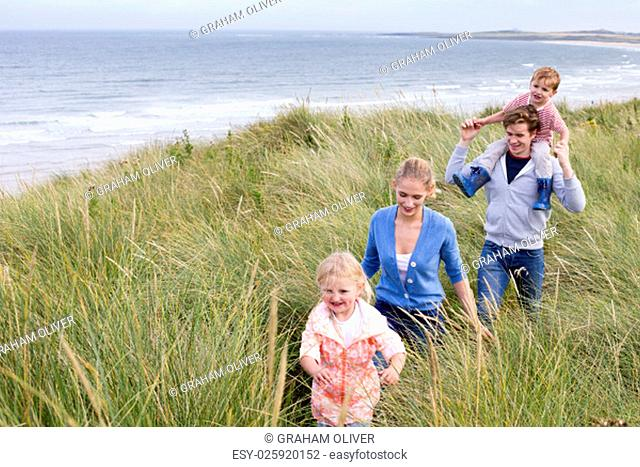 A young family of four walking through long grass next to the beach. They are wearing casual clothing and are smiling