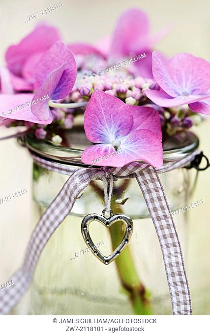 Hydrangea flowers in glass vase decorated with a metal heart and ribbon