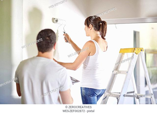 Couple painting the wall in new home