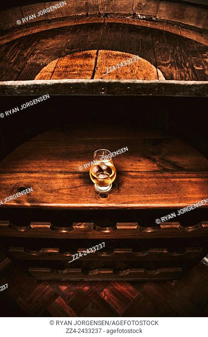 Aged glass of rum sitting on an old oak cellar barrel. Distillery tours