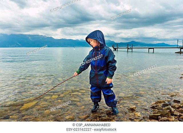 Cute little boy playing by the lake, pretending fishing, wearing blue waterpoof all-in-one suit and rain boots
