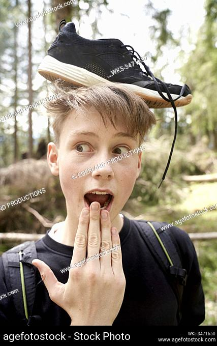 Young boy in forest with sneaker on his head. Bad Tölz, Upper bavaria, Germany