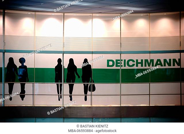 The illuminated logo with model papercuts of the shoe wholesale seller Deichmann in the Berlin Ostbahnhof