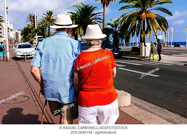 Elder couple walking on Promenade des Anglais. Nice, Alpes-Maritimes, French Riviera, Provence-Alpes-Côte d'Azur, France