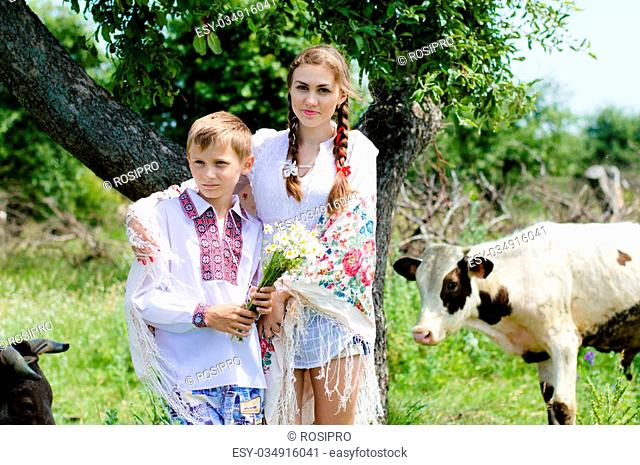 Teenage sister and little brother standing by cow herd in meadow on summer day