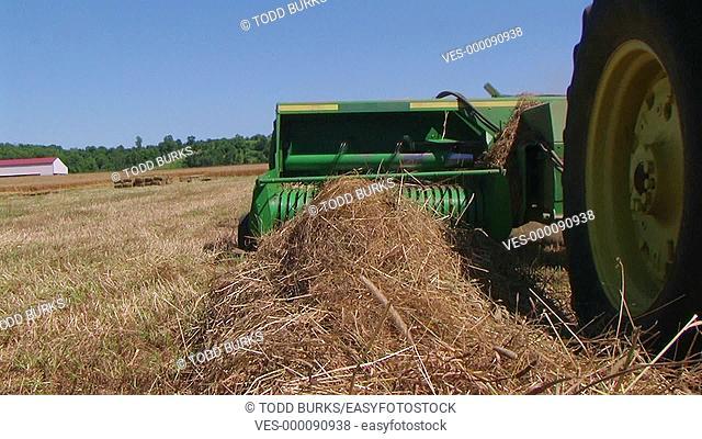 Square baling hay with accumulator, crane shot