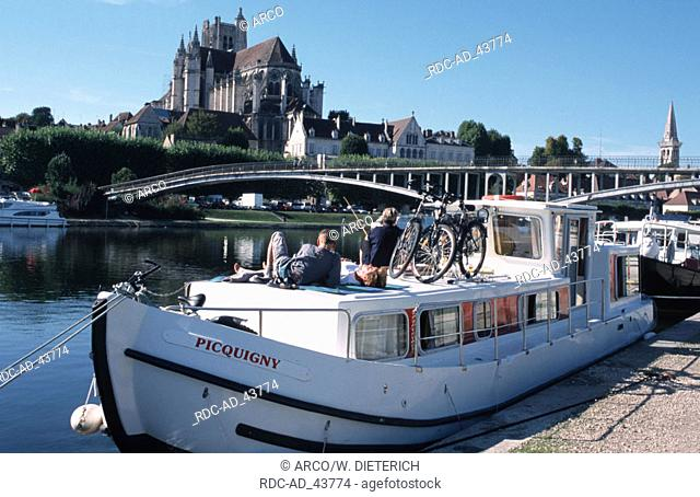 Housboat on river Yonne in front of church St. Etienne Auxerre Burgundy France