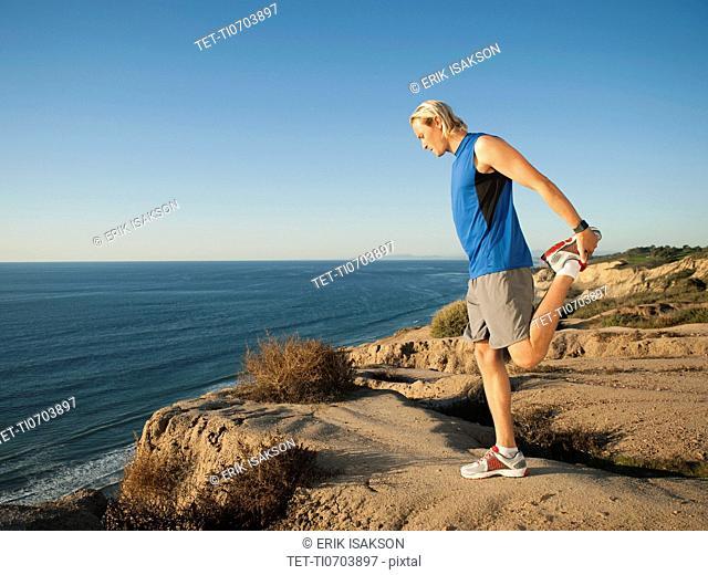 USA, California, San Diego, Man stretching at sea coast