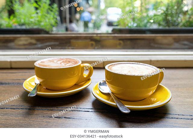Two cups of coffee next to the window in a cafe