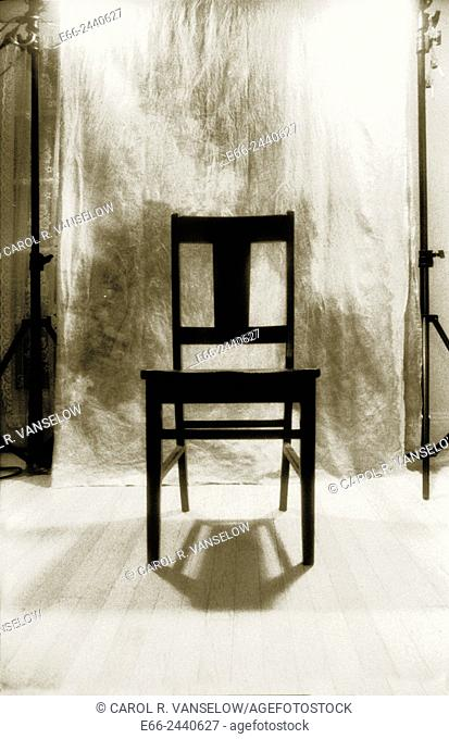 Black and white infrared shot of black chair in front of backdrop in studio