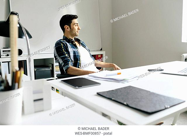 Young man with tablet and notes at desk in office thinking