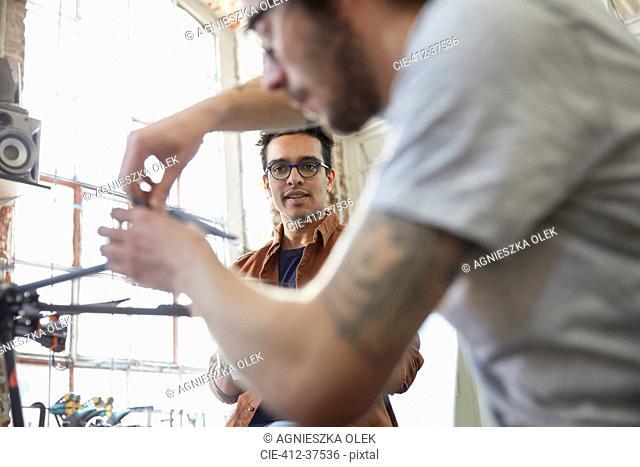 Male designers assembling drone in workshop
