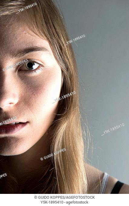 Tilburg, Netherlands. Studio-portrait of a young woman against a grey background. Detailed image