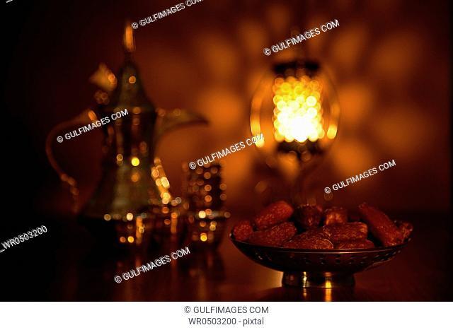Dates with tea set and illuminated lantern