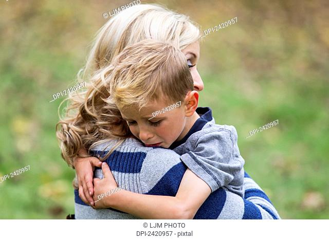 A young boy who is hurt and seeks comfort from his mother; Edmonton, Alberta, Canada