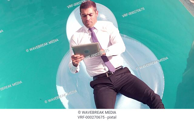 Businessman using tablet pc on inflatable