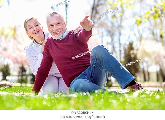 Look there. Delighted aged man pointing with his hand while showing something interesting to his wife