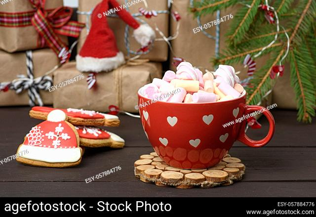 red ceramic cup with cocoa and marshmallows, behind a gift box and a Christmas toy