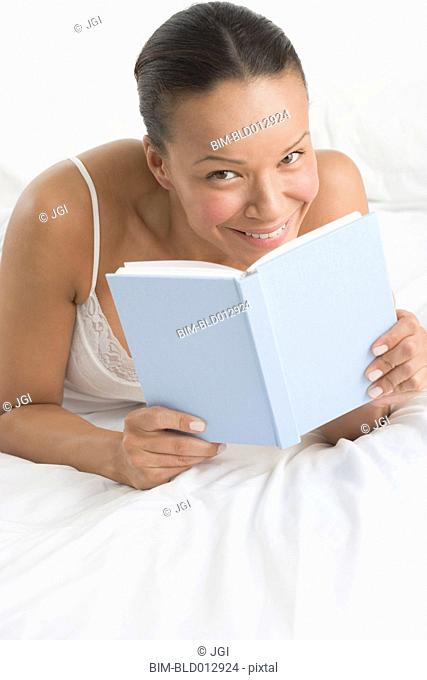Portrait of woman laying on bed reading book