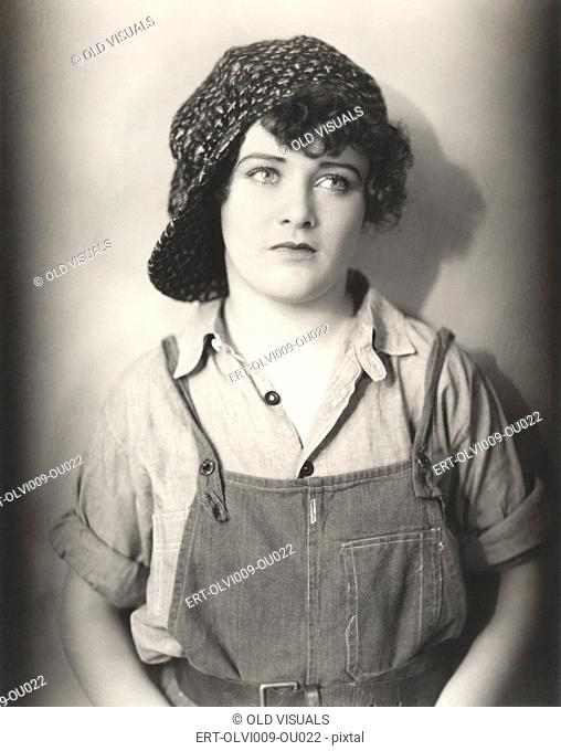 Woman in backwards cap and bib overalls