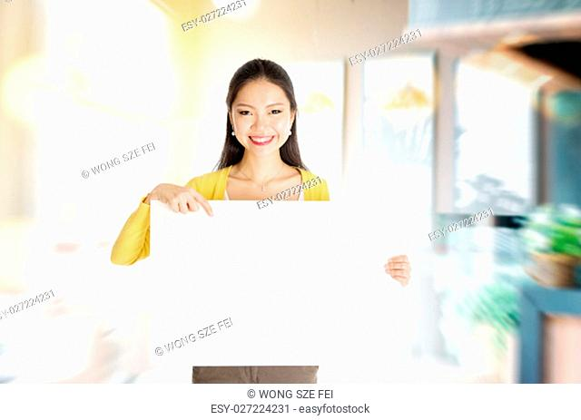 Young Asian woman hand holding a blank white paper card standing in her cafe. Copy space ready for text