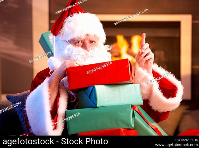 Portrait of Santa Claus sitting by fireplace holding a pile of Christmas presents