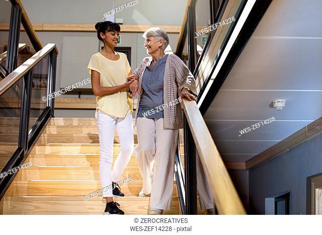 Nurse helping senior woman to walk down the stairs