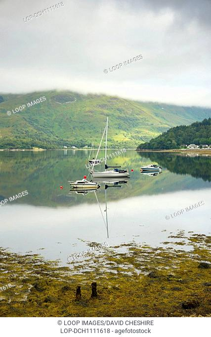 Boats moored on a flat calm Loch Leven