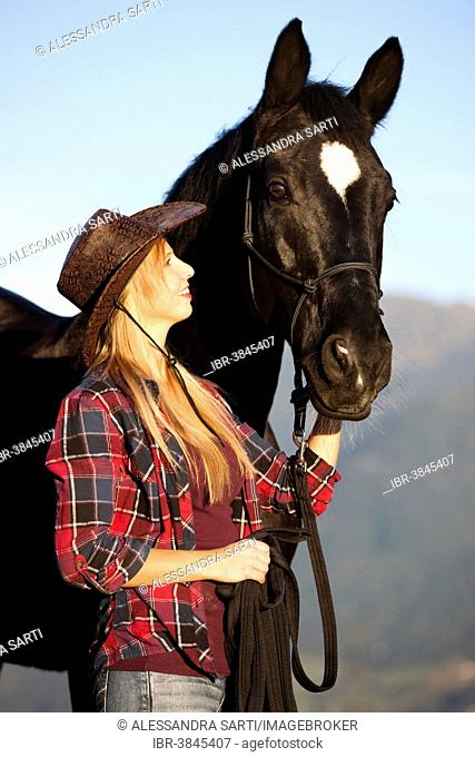 Young woman with a black Hanoverian horse, North Tyrol, Austria