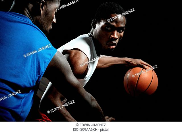 Male basketball players competing for ball