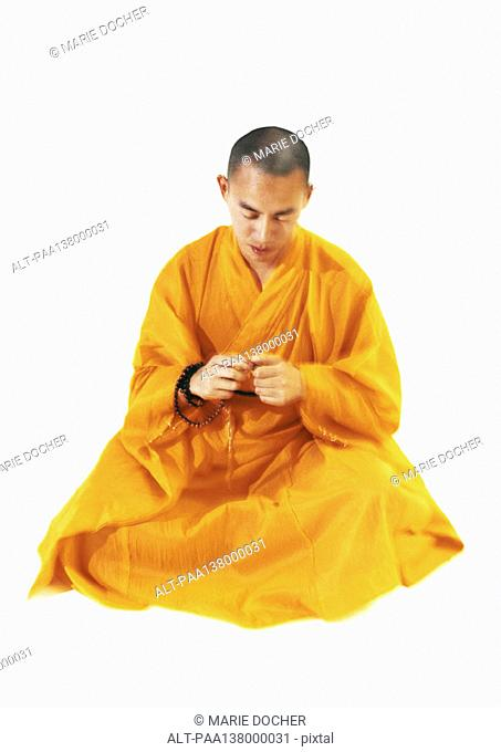 Buddhist monk sitting and meditating, holding prayer beads