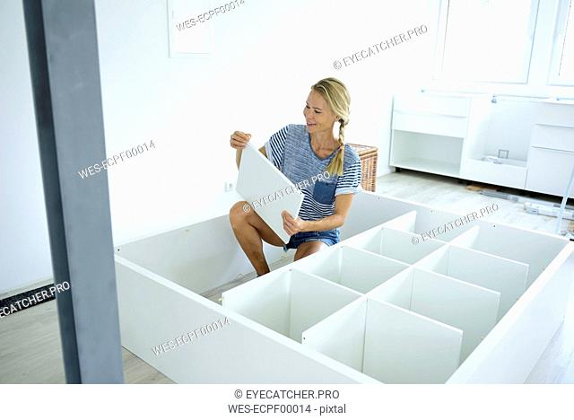 Woman assembling cabinet at home