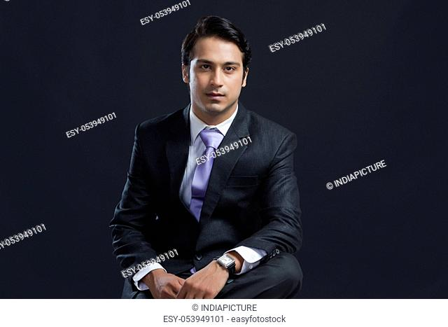Portrait of confident young businessman against black background