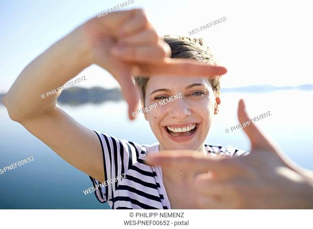 Portrait of laughing woman in front of lake shaping frame with her fingers
