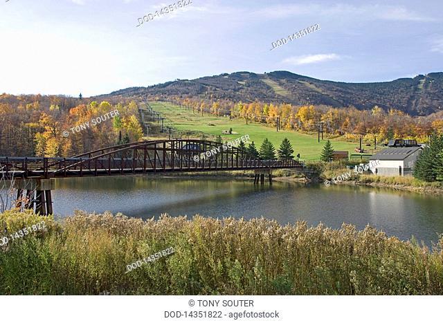 USA, Vermont, Green Mountains, Killington ski slopes with bridge over river in autumn