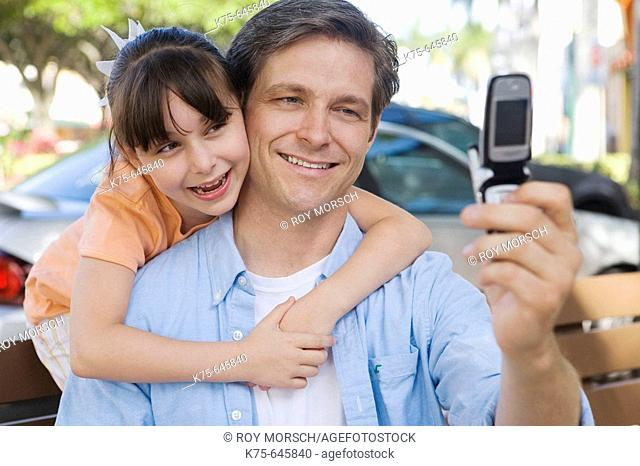 caucasians; dad age 30 to 40, daughter, age 9, camera phone, smiling, hugging